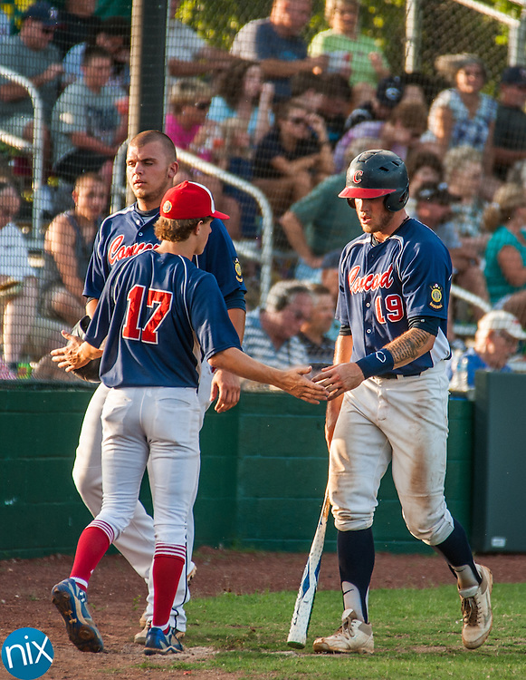 Concord Post 51's Parker Henderson and Nick Coble are greeted by Kaleb Measimer after scoring against Rowan County Tuesday night at Central Cabarrus High School. Concord won the game 7-6 in the second game of a best-of-five game playoff series.