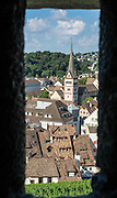 Through a window in Munot fortress, admire a panorama of vineyards and Schaffhausen's Old Town, a patchwork of rooftops and spires, in Switzerland, Europe. The Münster zu Allerheiligen / All Saints' Minster Church was built in 1103 (replacing the first church built in 1049).