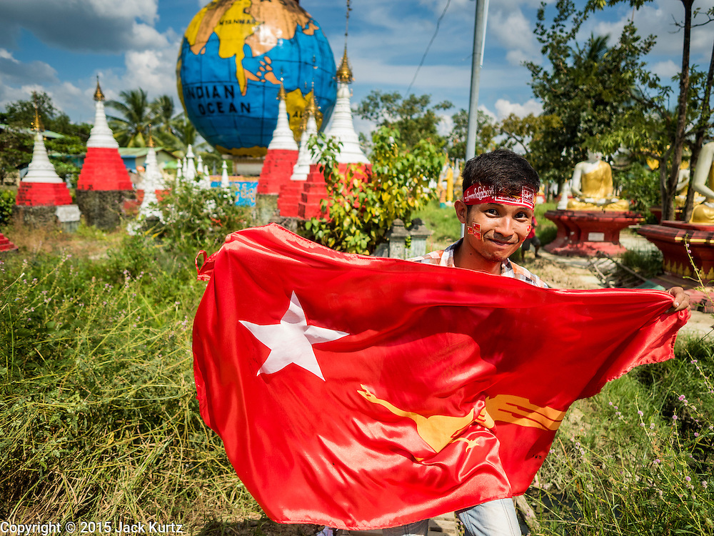 01 NOVEMBER 2015 - YANGON, MYANMAR: Supports of the NLD walk with a NLD banner across a small creek to get to the NLD's last election rally of the 2015 election in the Yangon suburbs Sunday. Political parties are wrapping up their campaigns in Myanmar (Burma). National elections are scheduled for Sunday Nov. 8. The two principal parties are the National League for Democracy (NLD), the party of democracy icon and Nobel Peace Prize winner Aung San Suu Kyi, and the ruling Union Solidarity and Development Party (USDP), led by incumbent President Thein Sein. There are more than 30 parties campaigning for national and local offices.    PHOTO BY JACK KURTZ