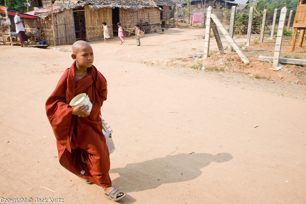 26 FEBRUARY 2008 -- MYAWADDY, MYANMAR: A novice monk walks through Myawaddy, Myanmar, during his morning rounds for alms. Myawaddy, a town of about 65,000, is just across the Moei River from Mae Sot, Thailand and is one of Myanmar's leading land ports for goods going to and coming from Thailand. Most of the businesses in the town are geared towards trade, both legal and illegal, with Thailand. Human rights activists from Myanmar maintain that the Burmese government controls the drug smuggling trade between the two countries and that most illegal drugs made in Myanmar are shipped into Thailand from Myawaddy.   Photo by Jack Kurtz