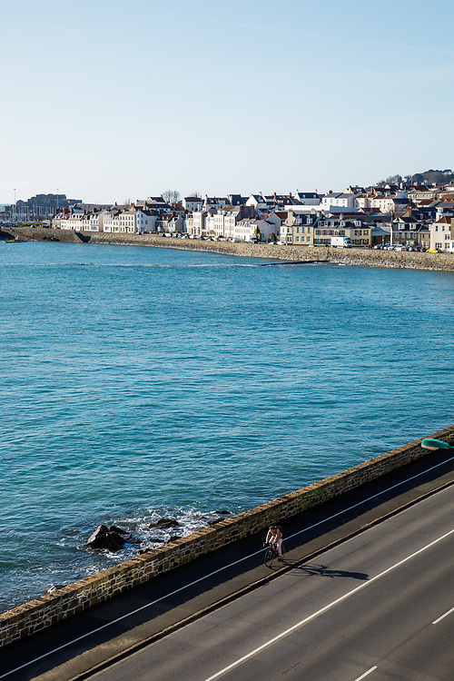 Beachfront housing in St Peter Port town overlooking the sea at high tide on a summers day in Guernsey, CI