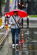 "People walk in the City of London as heavy rain batters the capital, in London, Friday, Oct. 2, 2020. Britain is facing gales and heavy downpours as the storm ""Alex"" in reaching its coasts. (VXP Photo/ Vudi Xhymshiti)"