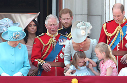 (Left to right) Queen Elizabeth II, Duchess of Sussex, Prince of Wales, Duke of Sussex, Duchess of Cambridge holding Princess Charlotte and Duke of Cambridge with Savannah Phillips on the balcony of Buckingham Palace, in central London, following the Trooping the Colour ceremony at Horse Guards Parade, as the Queen celebrates her official birthday.