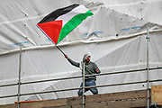 London, United Kingdom, May 15, 2021: A man waves a Palestinian flag as he stands on a construction site during a pro-Palestinian rally outside the Israeli Embassy in central London on Saturday, May 15, 2021. This is the 3rd week of ongoing demonstrations across the United Kingdom with 25 demonstrations taking place across the country today. (Photo by Vudi Xhymshiti/VXP)