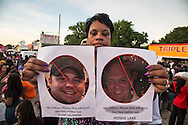 Evangelist Frankie Smith holding up photographs of the two officers that were involved in the shooting of Alton Sterling at a vigil for Alton Sterling at the Triple S Food Mart, Wednesday, July 6, 2016.