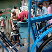 A bicycle rickshaw passes by a street food vendor selling cooked chick peas  (chhole kulcha) in Old Delhi