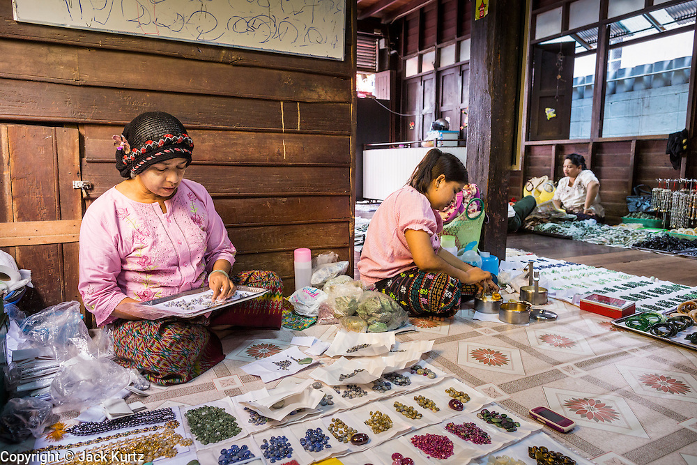 23 MAY 2013 - MAE SOT, TAK, THAILAND:  A Burmese Muslim woman and other Burmese women in a shop that rents floor space to gem dealers in Mae Sot, Thailand. There is a thriving business in buying and selling gems and precious stones in Mae Sot. Many of the gems are smuggled into Thailand from Myanmar. Fifty years of political turmoil in Burma (Myanmar) has led millions of Burmese to leave their country. Many have settled in neighboring Thailand. Mae Sot, on the Mae Nam Moei (Moei River) is the center of the Burmese emigre community in central western Thailand. There are hundreds of thousands of Burmese refugees and migrants in the area. Many live a shadowy existence without papers and without recourse if they cross Thai authorities. The Burmese have their own schools and hospitals (with funding provided by NGOs). Burmese restaurants and tea houses are common in the area.    PHOTO BY JACK KURTZ