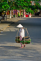 Woman walking up the road carrying baskets on her shoulders.