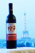 Bottle of 1907 Madiran Fruit and Passion against a pale blue background view over Paris with the Eiffel Tower Madiran France