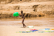 Young Nyangatom boy does the washing in the river. Omo Valley, Ethiopia