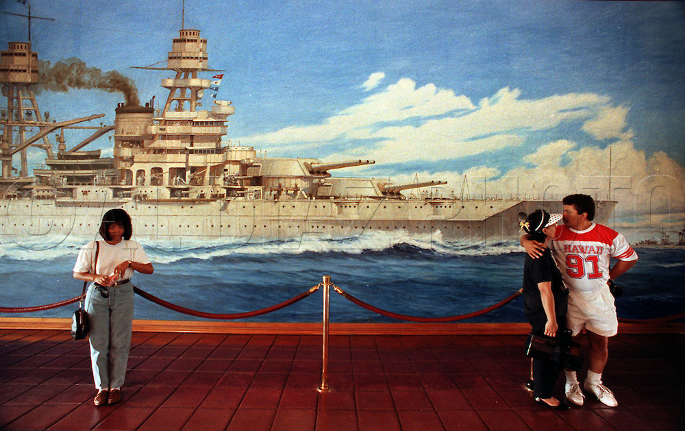 Al Diaz/Herald Staff--A large mural of the battleship Arizona in its heyday forms a backdrop for visitors to the Arizona Memorial Visitors Center in Hawaii