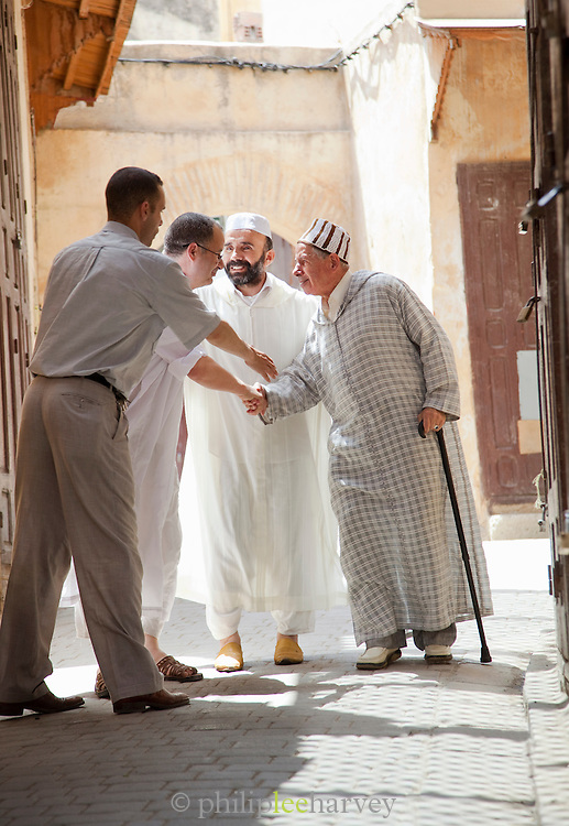 Men greet each other after prayer in the medina of Fes, Morocco