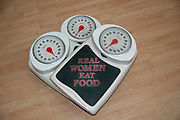 "Dieting, weight loss and body image conceptual image of three analogue scales stacked one on top of the other with the text of ""Real Women eat food"""