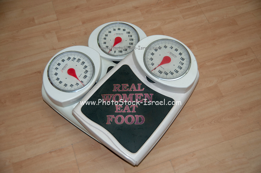 """Dieting, weight loss and body image conceptual image of three analogue scales stacked one on top of the other with the text of """"Real Women eat food"""""""
