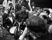 Muhammad Ali In Dublin..1972..11.07.1972..07.11.1972..11th July 1972..Prior to his fight against Al 'Blue' Lewis at Croke Park, Dublin, former World Heavyweight Champion, Muhammad Ali arrives at Dublin Airport..The fight was part of his build up for for a championship fight against the current World Champion, 'Smokin'  Joe Frazier. Ali had been stripped of the title partly due to his refusal to join the American military during The Vietnam War,which he had opposed...Photo of Muhammad Ali being mobbed by fans and the media on the tarmac at Dublin Airport. Included in the picture are some members of The Emerald Girls Pipe Band.