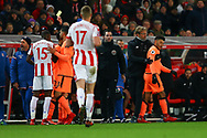 Bruno Martins Indi of Stoke City (l) receives a yellow card from referee Martin Atkinson as Liverpool Manager Jurgen Klopp has his arm around Alex Oxlade-Chamberlain of Liverpool (r). Premier league match, Stoke City v Liverpool at the Bet365 Stadium in Stoke on Trent, Staffs on Wednesday 29th November 2017.<br /> pic by Chris Stading, Andrew Orchard sports photography.