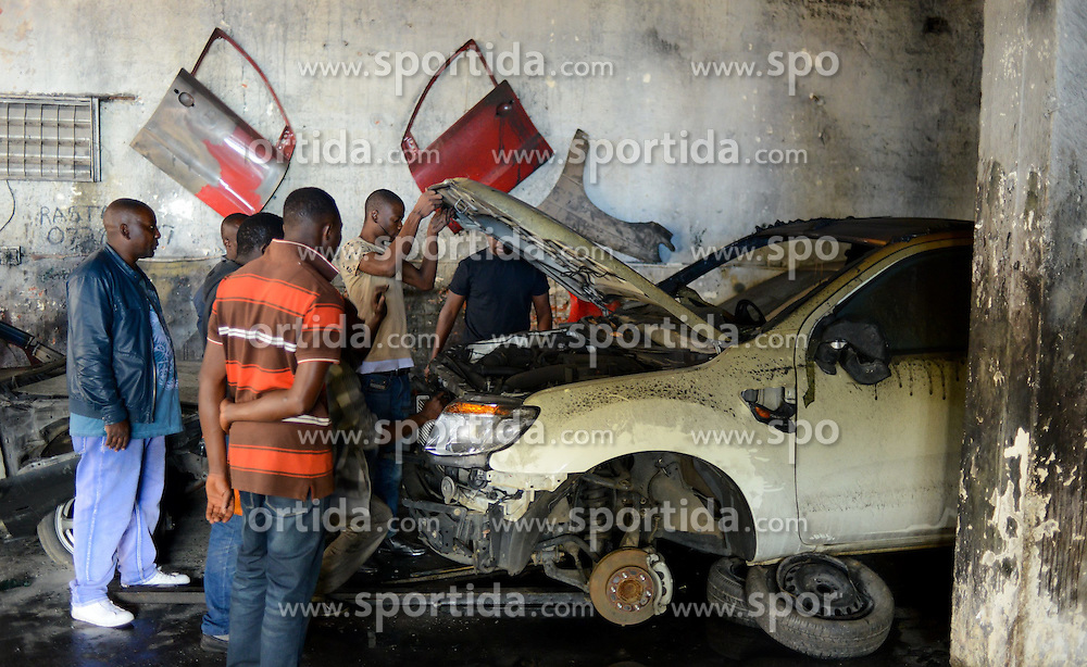 People check a burnt vehicle at a Nigerian-owned garage in Johannesburg Town, South Africa, on April 17, 2015. South African police on Friday fired rubber bullets to disperse rioters in central Johannesburg, a fresh hotbed of xenophobia violence. The current spate of xenophobic violence mainly affects Durban and Johannesburg. According to official figures, five people have been killed and thousands of immigrants displaced. EXPA Pictures © 2015, PhotoCredit: EXPA/ Photoshot/ Zhai Jianlan<br /> <br /> *****ATTENTION - for AUT, SLO, CRO, SRB, BIH, MAZ only*****