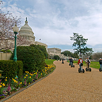 A group rides Segway personal transporters past the U.S. Capitol building, blooming cherry trees and spring garden flowers in Washington, D.C.