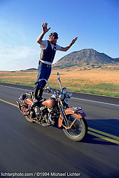 """Puppy and Bear Butte, Sturgis, SD. 1994<br /> <br /> Limited Edition Print from an edition of 50. Photo ©1994 Michael Lichter.<br /> <br /> The Story: I have photographed quite a few bikers surfing like this, but on this occasion and in this frame, Puppy exuded the spirit of what biking is all about as he rides his Flathead past Bear Butte. A friend of mine captured that spirit when she looked at this image and said, """"Feel the Freedom""""."""