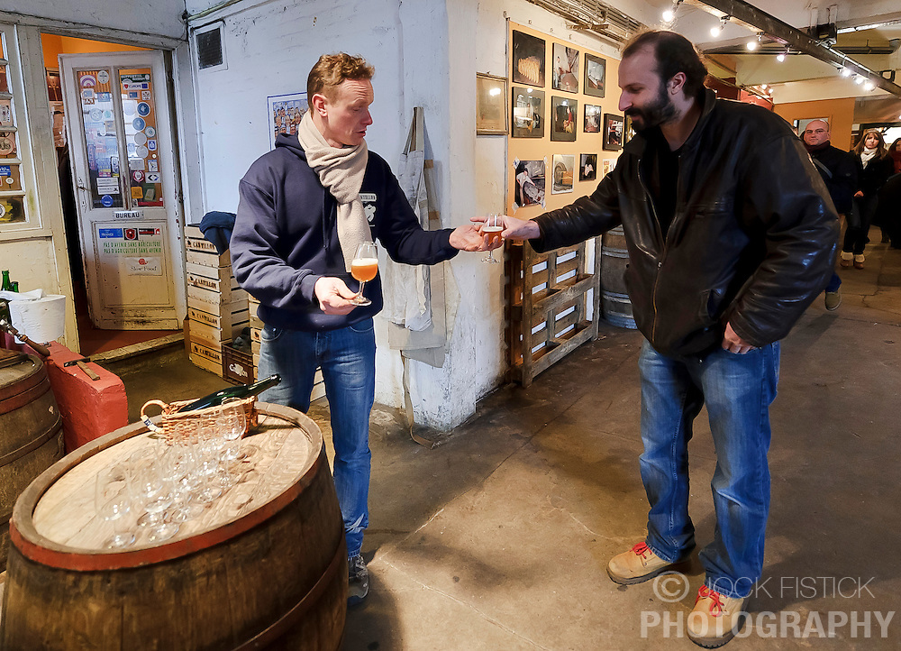 BRUSSELS, BELGIUM - DEC-30-2010 -  Jean Van Roy, the fourth generation owner of the Brasserie Cantillon, left, offers a sample of Gueze to Stephane Chabert, of Savoie, France, a visitor to the working brewery and museum of Belgian beer history. Cantillon specialises in a unique, wine-like style of beer called Lambic in its most elemental form, and Gueze when it's blended. The sour beer gets its funky, acidic bite from a spontaneous fermentation process and long aging that inoculates the wort, or pre-beer, with bacteria and yeast naturally available in the air. Variations include batches aged with cherries (Kriek), raspberries (Rose de Gambrinus), and apricots (Fou'Foune), all produced organically and all 100 percent Lambic. (Photo © Jock Fistick)