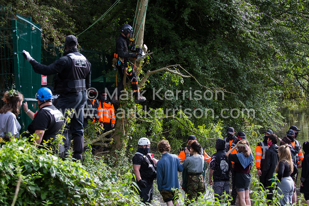 Denham, UK. 7th September, 2020. A large section of branch cut from a tree by a tree surgeon working on behalf of HS2 Ltd falls close to security workers and HS2 Rebellion activists taking direct action to prevent or delay tree felling works in conjunction with the HS2 high-speed rail link in Denham Country Park. Anti-HS2 activists continue to campaign and take direct action against the controversial £106bn project for which the construction phase was announced on 4th September from a series of protection camps based along the route of the line between London and Birmingham.