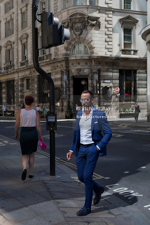 A stylish businessman wearing mirrored sunglasses and City architecture during the 2018 heatwave in the City of London, the capital's historic financial district, on 2nd August 2018, in London, England.
