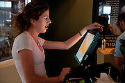 Israel, Tel Aviv, an outdoor cafe Waitress enters an order at a computerized till