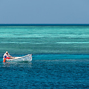A man and his son explore the coral from a small dinghy on Swains Reef on the Great Barrier Reef. The small boy is using an underwater viewer over the side of the boat to see clearly below the water from above. The green area behind them is the shallow water of the reef. The blue water closer to the camera is deeper water.