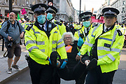 Metropolitan Police officers arrest an Extinction Rebellion activist who had taken part in a pink roadblock of Oxford Circus by women and FINT-identifying environmental activists during the third day of Impossible Rebellion protests on 25th August 2021 in London, United Kingdom. Extinction Rebellion are calling on the UK government to cease all new fossil fuel investment with immediate effect.