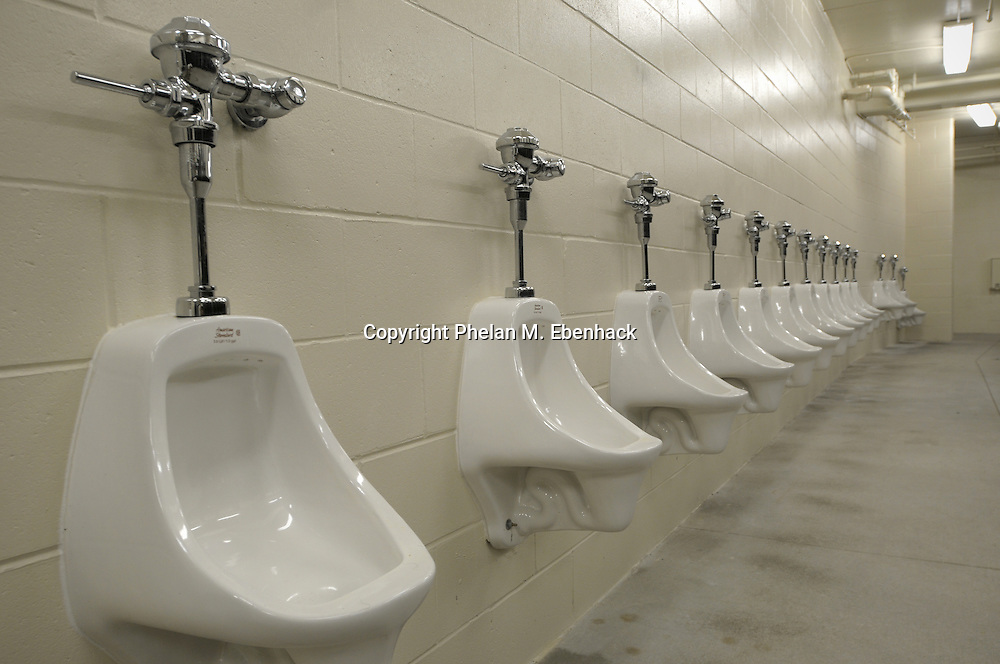 A set of urinals line the wall of a stadium men's restroom.