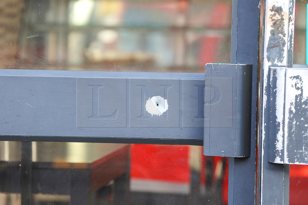 © Licensed to London News Pictures. 18/09/2019. London, UK. Possible gunshot on the door of Sweet Peppa - a Jamaican Cuisine on Lordship Lane near Wood Green underground station in North London following a shooting at 9.50pm on Tuesday, 17 September. A short time later, a 46-year-old woman and a 31-year-old man presented themselves at hospital. The woman had sustained a gunshot injury and her condition has been assessed as critical. The condition of the 31-year-old man is not life-threatening or life-changing. He is thought to have sustained a minor gunshot injury. Photo credit: Dinendra Haria/LNP