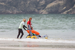 A disabled child using an amphibious wheelchair at Fistral Beach in Newquay, Cornwall.