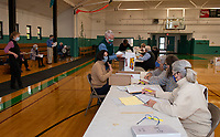 Absentee and mail in ballots go through ballot verification on Thursday morning at the Laconia Community Center.  (Karen Bobotas Photo/for The Laconia Daily Sun)