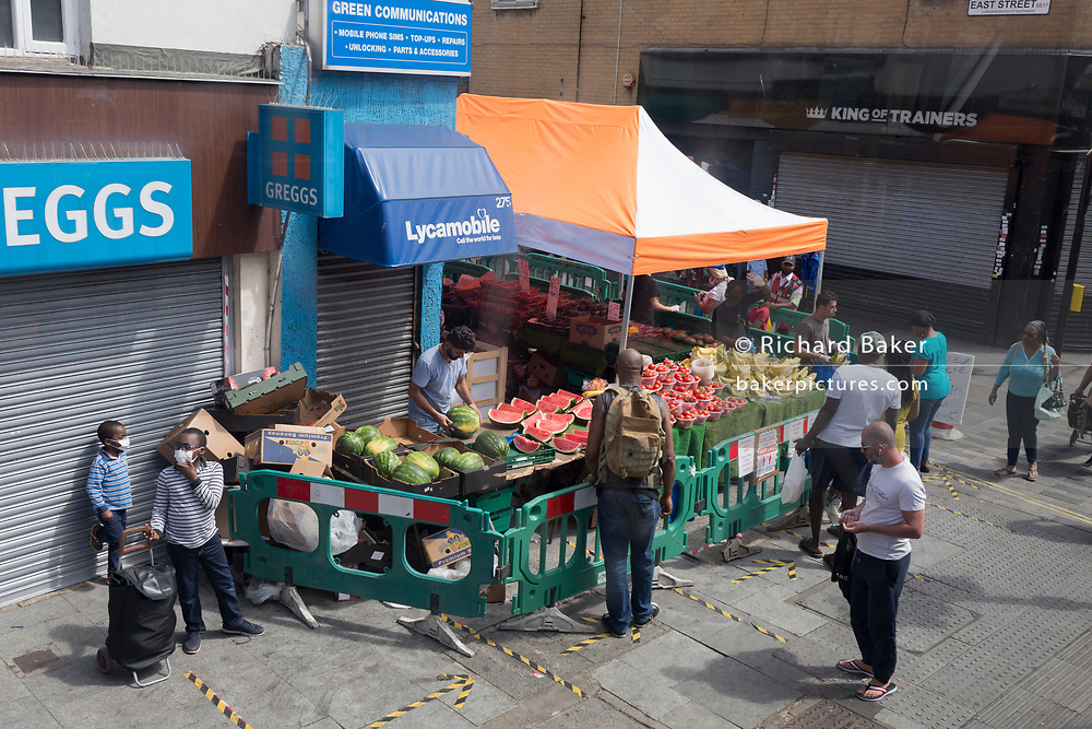 During the UK's Coronavirus pandemic lockdown and on the day when a further 255 deaths occurred, bringing the official covid deaths to 37,048, <br /> shoppers at a fruit and veg stall practice social distancing at East Street Market on the Walworth Road, on 26th May 2020, in London, England.