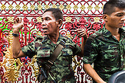 "09 AUGUST 2014 - BANGKOK, THAILAND: Thai soldiers direct people coming into the Ruby Goddess Shrine in the Dusit section of Bangkok for a Ghost Month community meal. The seventh month of the Chinese Lunar calendar is called ""Ghost Month"" during which ghosts and spirits, including those of the deceased ancestors, come out from the lower realm. It is common for Chinese people to make merit during the month by burning ""hell money"" and presenting food to the ghosts. At Chinese temples in Thailand, it is also customary to give food to the poorer people in the community.        PHOTO BY JACK KURTZ"