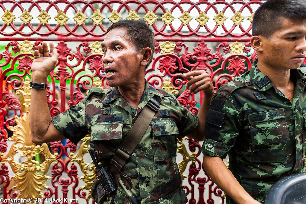 """09 AUGUST 2014 - BANGKOK, THAILAND: Thai soldiers direct people coming into the Ruby Goddess Shrine in the Dusit section of Bangkok for a Ghost Month community meal. The seventh month of the Chinese Lunar calendar is called """"Ghost Month"""" during which ghosts and spirits, including those of the deceased ancestors, come out from the lower realm. It is common for Chinese people to make merit during the month by burning """"hell money"""" and presenting food to the ghosts. At Chinese temples in Thailand, it is also customary to give food to the poorer people in the community.        PHOTO BY JACK KURTZ"""