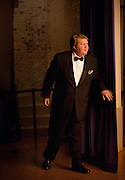 An opera singer dressed for his performance peaks past the curtain at the incoming crowd.