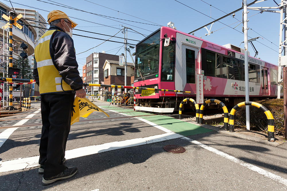 A school crossing guard watches a tram on the Toden Arakawa Line, known as the Tokyo Sakura Tram, at a crossing near Oji in Tokyo, Japan. Wednesday March 24th 2021