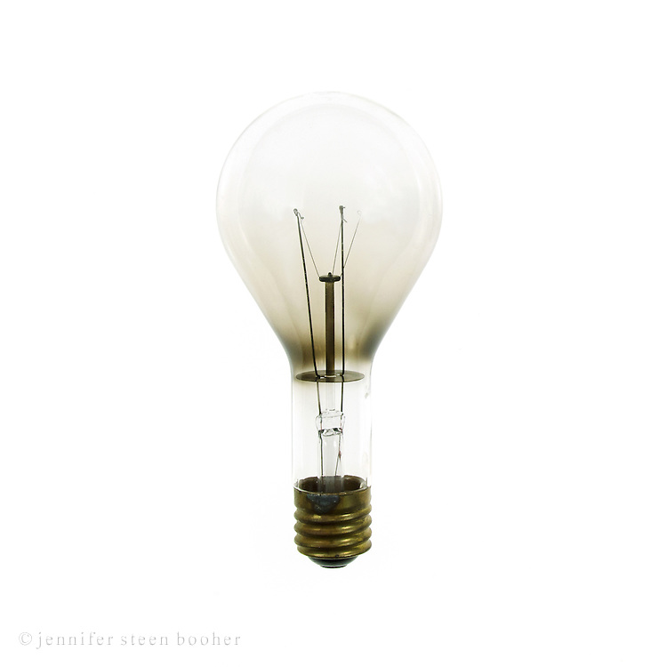 A single oversized antique industrial lightbulb on a white background.
