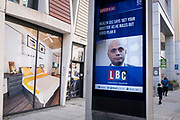 On the day that the UK has recorded 50,000 Covid cases, the first time in three months, Conservative MP and government Health Secretary, Sajid Javid appears on a news screen in the East End, with the latest headline about his refusal to ask the public to wear face coverings, or to further enforce Englands Plan B to control surging Covid cases despite appeals from leading doctors, and instead, for the public to simply have booster jabs, on 21st October 2021, in London, England  .