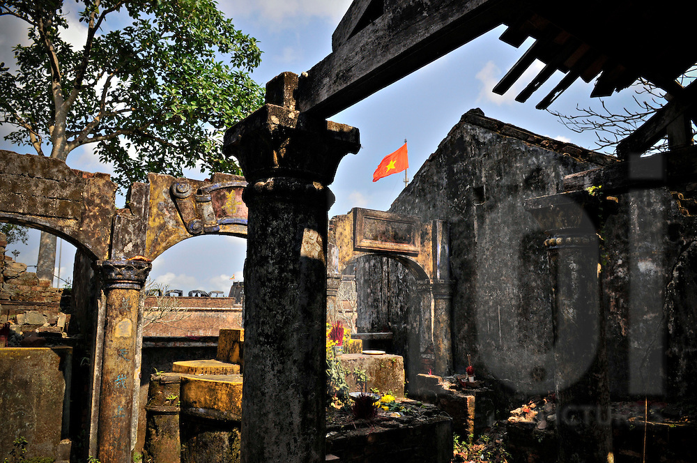 Weathered and deserted building with a Vietnamese flag visible in the background. Hue, Vietnam, Southeast Asia