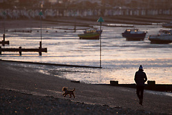 © Licensed to London News Pictures.27/03/2021. Southend-On-Sea,UK. A man walks his dog by the beach in Southend-On-Sea, Essex during the sunrise. Weather forecasts predict sunny weather with strong winds in the south-east of England.   Photo credit: Marcin Nowak/LNP