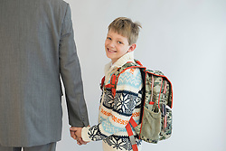 Father accompanying his son to school, smiling