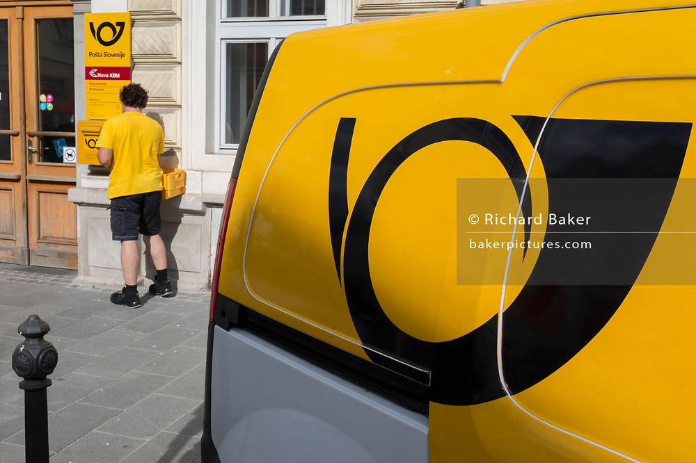A postman from the Slovenian postal service (Posta Slovenije) collects post from a post box outside the post office in rural Slovenia, on 26th June 2018, in Kamnik, Slovenia.