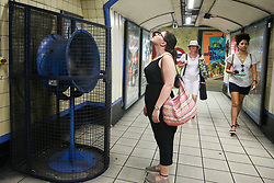 © Licensed to London News Pictures. 25/07/2019. London, UK. Concetta Ventura stands in front of a large fan at Manor House station cool down. According to the Met Office, today will be the hottest day of the year and temperatures are expected to break records. <br /> <br /> ***Permission Granted***<br /> <br /> Photo credit: Dinendra Haria/LNP
