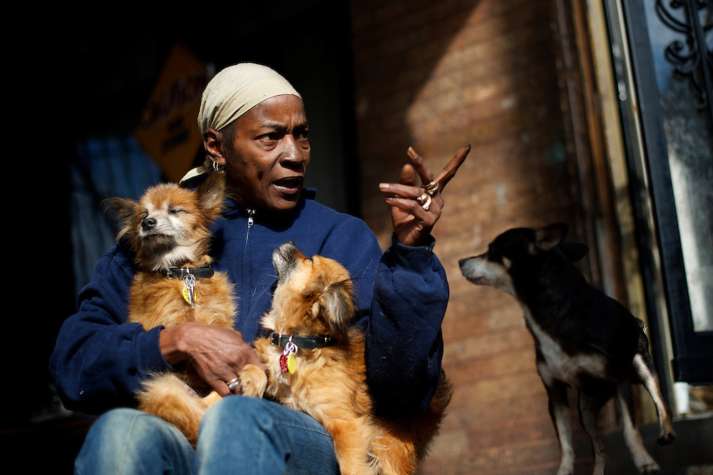 Betty Hill poses cradles her dogs on her front porch in Philadelphia.