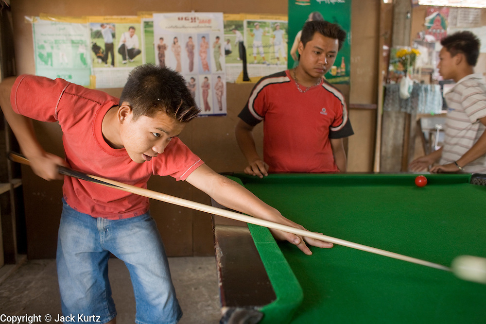 26 FEBRUARY 2008 -- MYAWADDY, MYANMAR: Pool players in a pool hall in Myawaddy, Myanmar (Burma). Pool was brought to Burma during the British colonial era and is now played throughout the country. Myawaddy is just across the Moei River from Mae Sot, Thailand and is one of Myanmar's leading land ports for goods going to and coming from Thailand. Most of the businesses in the town are geared towards trade, both legal and illegal, with Thailand. Human rights activists from Myanmar maintain that the Burmese government controls the drug smuggling trade between the two countries and that most illegal drugs made in Myanmar are shipped into Thailand from Myawaddy.   Photo by Jack Kurtz