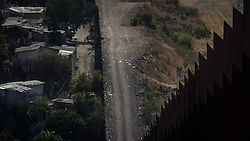 The US/Mexico border wall in Otay, Tijuana. Thousands of migrants pass over the wall in this region each year, and many go through the desert to reach the US, large numbers of them die along the way, of heatstroke or dehydration.