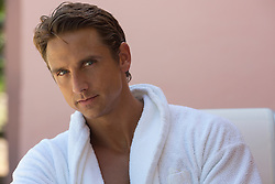 handsome forty something year old man in a white bathrobe