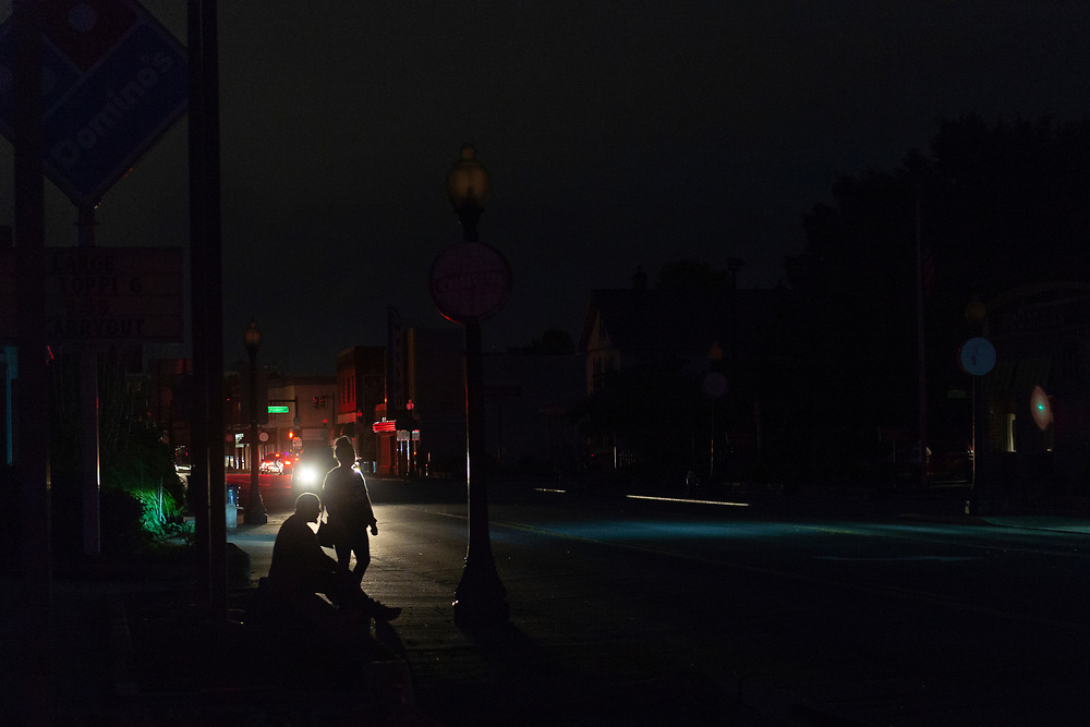 Two people are silhouetted by a passing car along an unlit Washington Street as power rained out after a tornado tore through Charleston, W.V., on June 24, 2019. (Craig Hudson/The Charleston Gazette-Mail via AP)